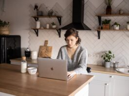 content young woman browsing laptop in modern kitchen